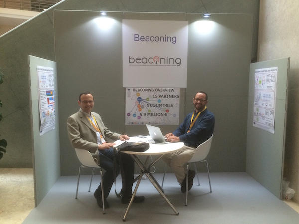 The BEACONING booth at Eurographics 2016, covered with 3 poster describing the project and a round table to receive guests. In this picture António Coelho from INESC TEC is talking to another researcher.